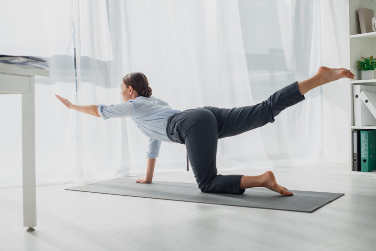 Businesswoman practicing yoga in bird dog pose on mat in office