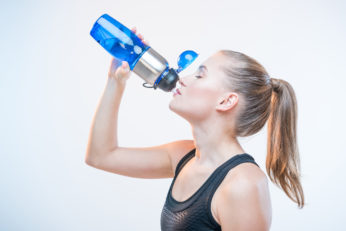 woman drinking from sports flask