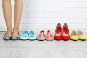 a pair of feet standing next to a line of footwears