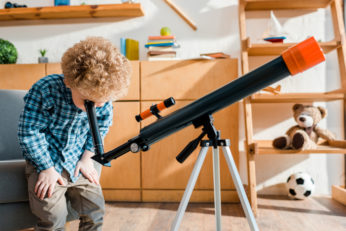 a boy looking through a magnifying instrument