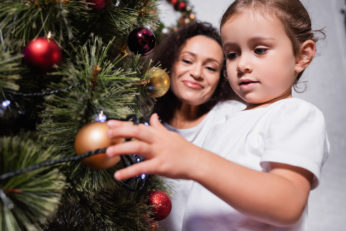 a mother and daughter decorating tree