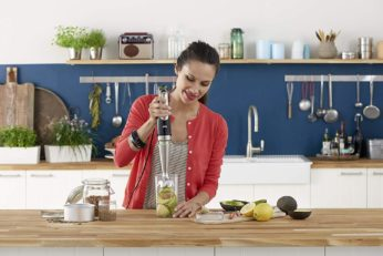 a woman making an smoothie