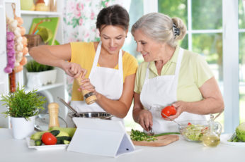 an elderly and a young lady cooking together