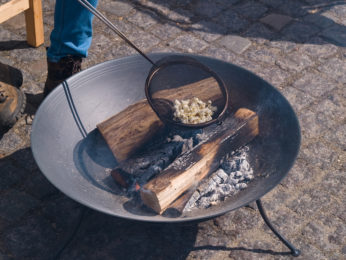 cooking popcorn over burning logs