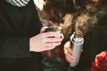couple drinking from stainless steel thermos