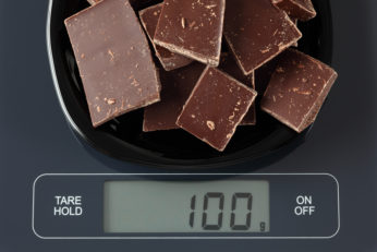 dark chocolate squares being weighed