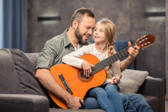 father and daughter playing a musical instrument