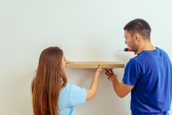 man and woman installing wall mounted rack