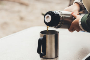 woman pouring coffee from stainless steel thermos