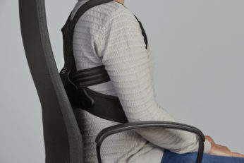 man wearing a posture corrector while sitting
