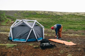 a hiker setting up a tent