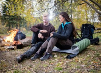 man with woman sitting on a runner during camping