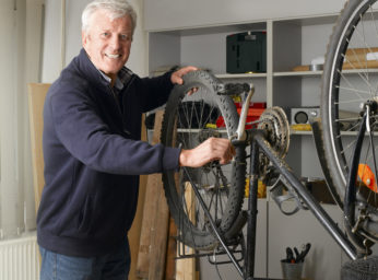 old man repairing bicycle