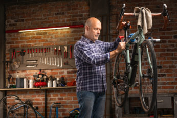 workman doing maintenance check on bicycle