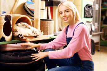young woman choosing a pet cushion in store