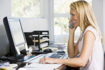 young woman using telephone in home office