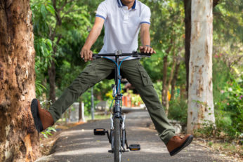 man playfully riding on bicycle