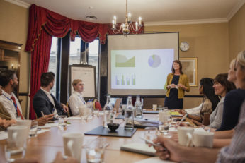 woman giving presentation before colleagues