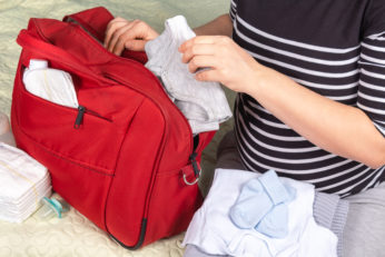 woman packing red diaper tote