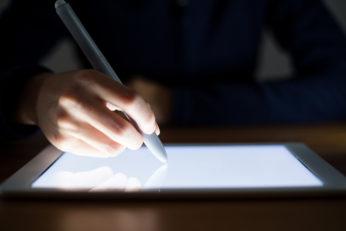 woman writing using stylus pen
