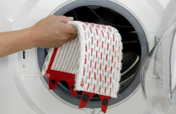 closeup of hand putting mircrofibre pad in washer