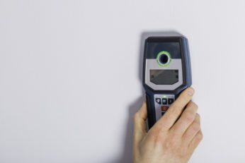 man hand is scanning wall using cable detector