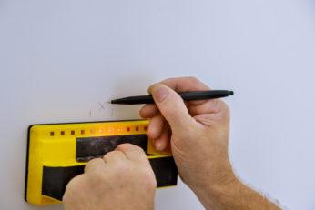 man hand scanning wall using digital detector