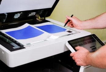 worker scanning documents on copier