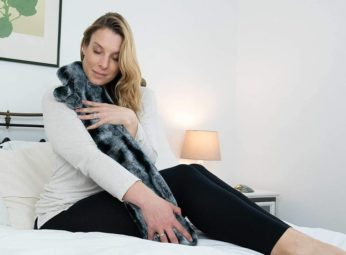 a woman holding a bed warmer
