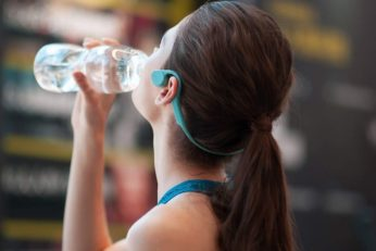 young woman drinking water with headset on