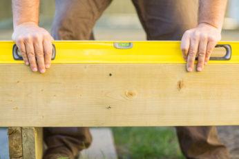 carpenter using tool on wood