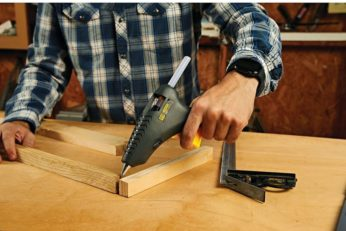 man glueing pieces of wood