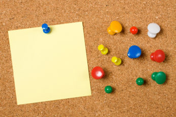 push pins and blank note on bulletin board