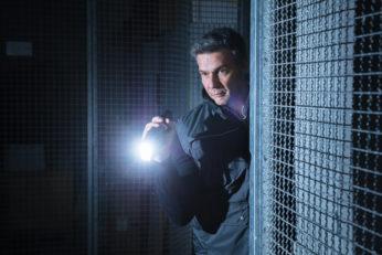 security guard using flashlight in the dark