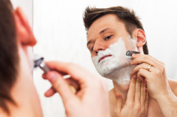young man shaving his beard in front of mirror