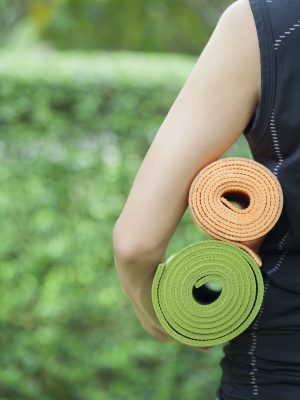 Young woman holding yoga mats